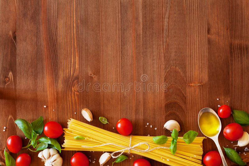 Espaguetis, tomate de cereza, albahaca, ajo y aceite de oliva crudos, ingredientes para cocinar las pastas, fondo de la comida foto de archivo