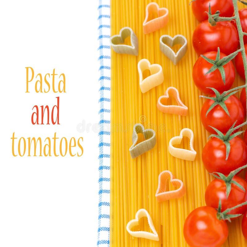 espaguetis, tomates de cereza y pastas bajo la forma de corazones imagen de archivo libre de regalías