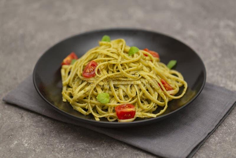 Espaguetis vegetarianos de las pastas con los tomates del pesto y de cereza de la albahaca imagenes de archivo
