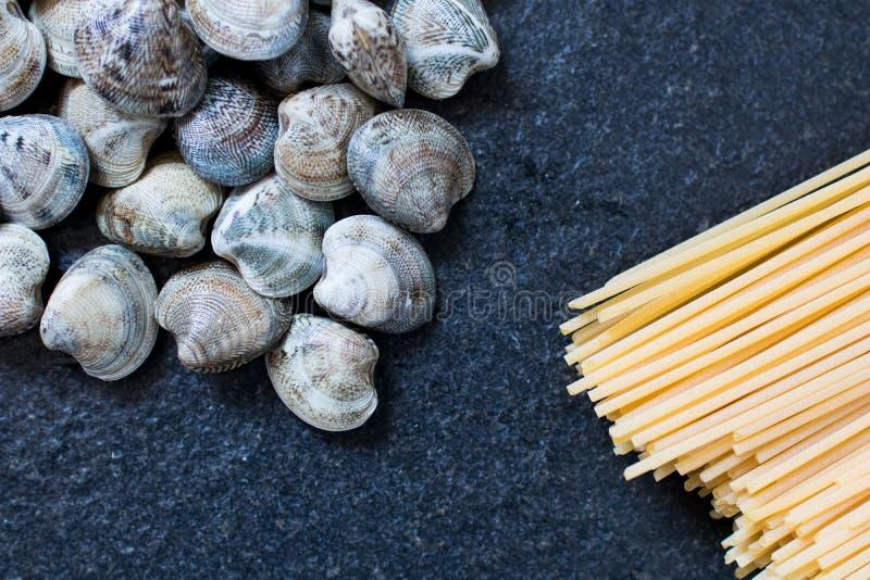 espaguetis y almejas en una tabla negra del granito, ingredientes del AIE fotografía de archivo