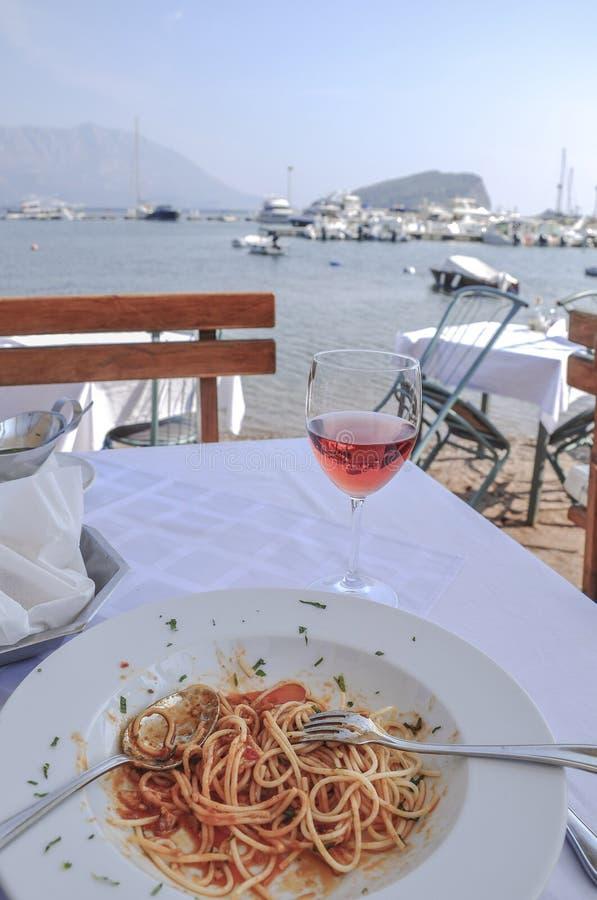 Espaguetis y copa de vino en la tabla por el mar foto de archivo libre de regalías