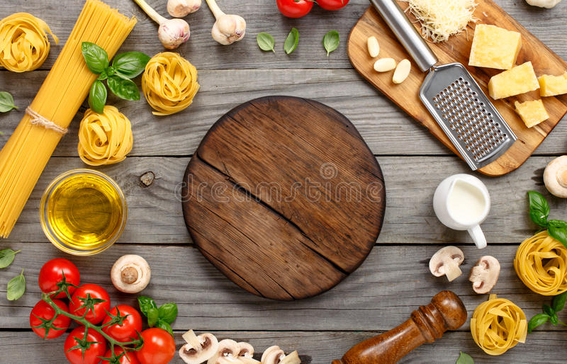 Espaguetis y fettuccine con los ingredientes para cocinar las pastas imagenes de archivo