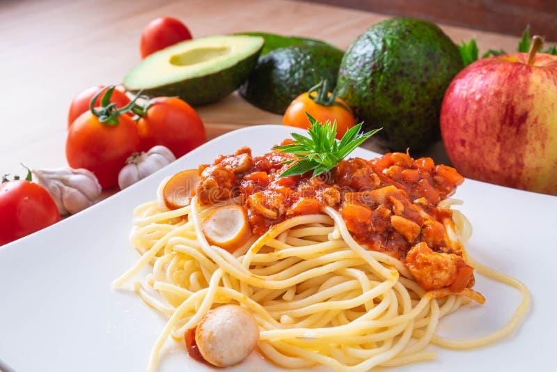 Espaguetis y tomates frescos con los condimentos en los tableros de madera fotos de archivo libres de regalías
