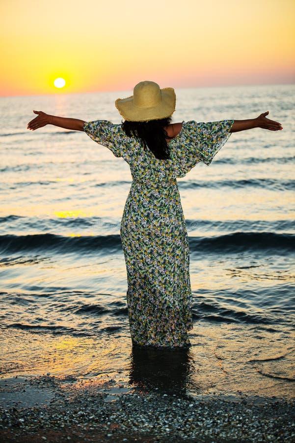 espalda-de-mujer-con-los-brazos-abiertos-al-sol-una-un-vestido-largo-y-que-en-el-mar-abrazando-amanecer-sinti%C3%A9ndose-libre-194706360.jpg