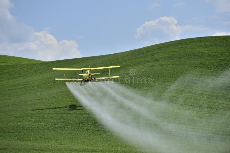 Espanador da colheita do biplano que pulveriza um campo de exploração agrícola. imagens de stock royalty free
