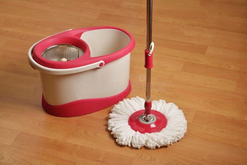 Espanador e cubeta de limpeza com o girador de secagem no assoalho de madeira foto de stock royalty free