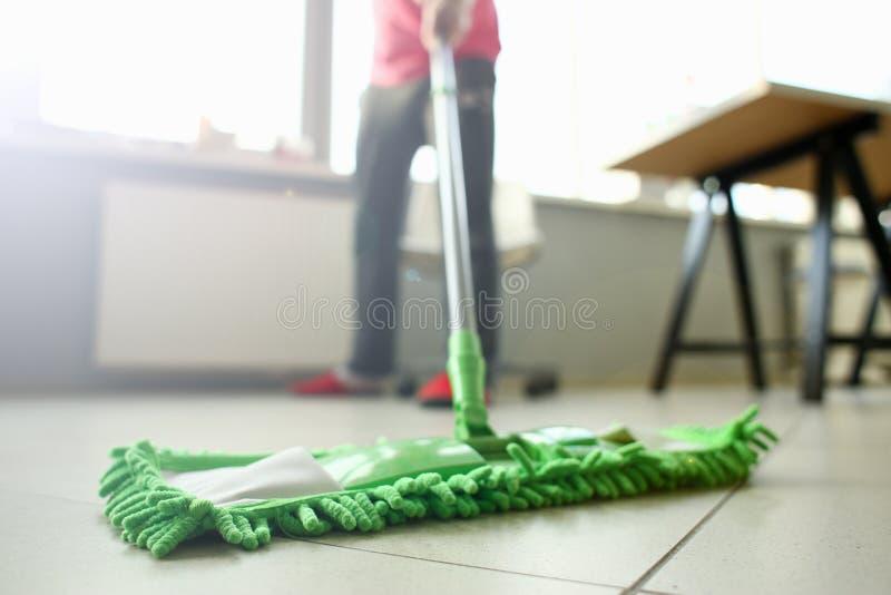 Espanador pl?stico verde que limpa o assoalho sujo claro laminado imagem de stock royalty free