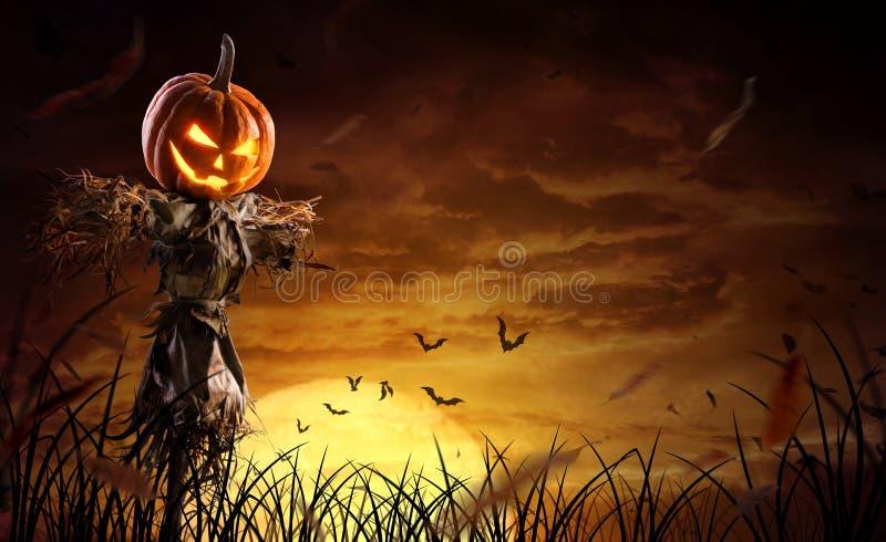 Espantapájaros de calabaza de Halloween en un amplio campo con la luna en una noche aterradora imagenes de archivo