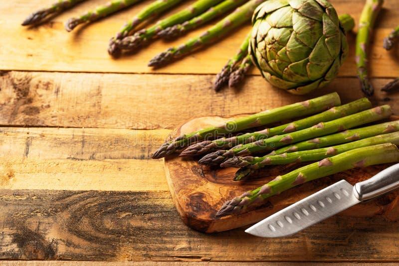 Espargos e uma alcachofra em uma placa de corte com uma faca, cortada no fundo de madeira Fundo culin?rio Dieta tasty imagens de stock royalty free