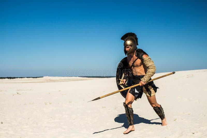 Espartano corre rapidamente através da areia imagem de stock