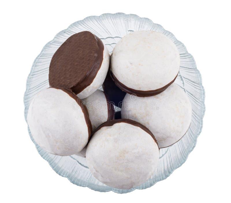 Especia-tortas esmaltadas con el chocolate en el cuenco aislado en blanco fotos de archivo libres de regalías