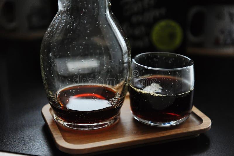 Especialidad en café negro alternativo servido con estilo Bandeja de bambú, decodificador de carafas y vidrio Café estético imagen de archivo