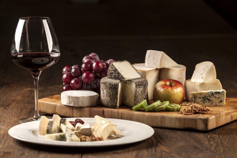 Especialidades da placa do vinho e de queijo fotografia de stock royalty free