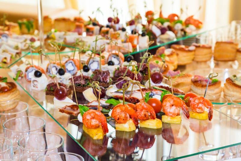 Especialidades dos petiscos, dos peixes e da carne no bufete Sobremesas Uma recepção da gala Tabelas seridas catering foto de stock royalty free