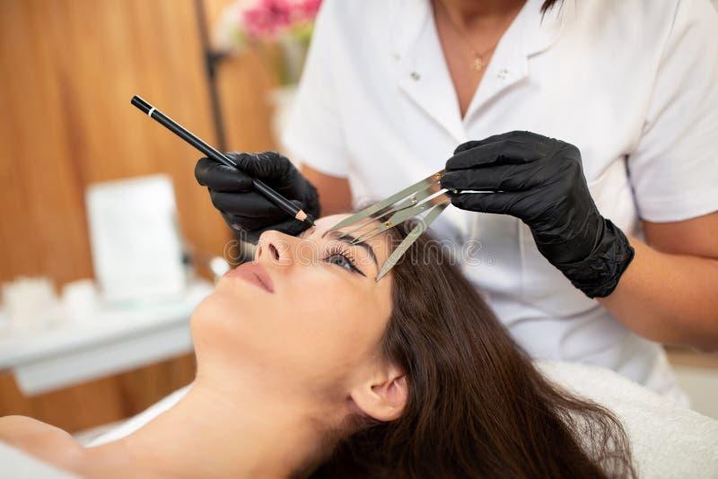 Especialista cosmético da tatuagem que usa ferramentas avançadas da mão imagem de stock