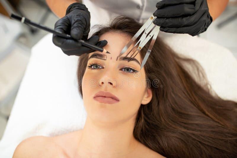 Especialista cosmético da tatuagem que usa ferramentas avançadas da mão fotos de stock royalty free