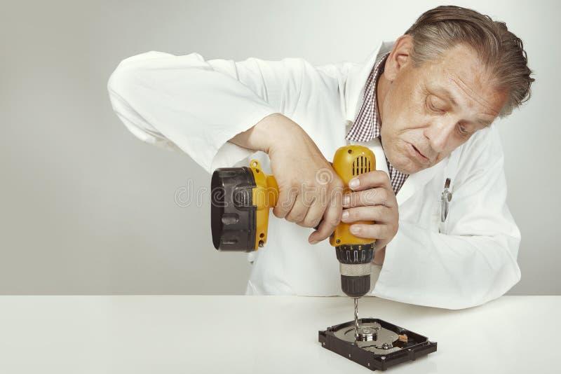 Especialista de la unidad de discos duros que borra datos de la unidad de discos duros con el taladro fotografía de archivo