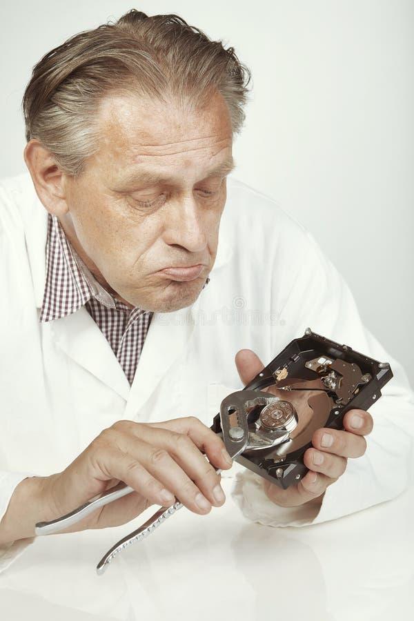 Especialista de la unidad de discos duros que borra datos de la unidad de discos duros con los alicates fotografía de archivo