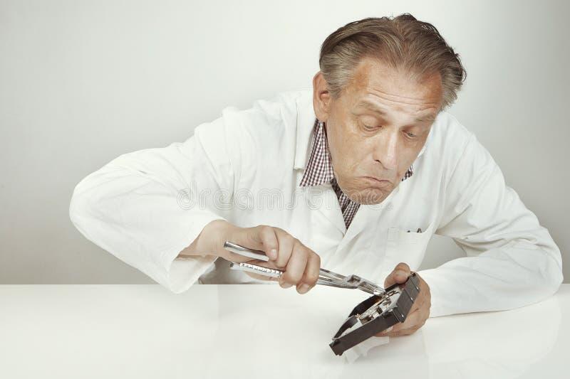Especialista de la unidad de discos duros que borra datos de la unidad de discos duros con los alicates foto de archivo libre de regalías