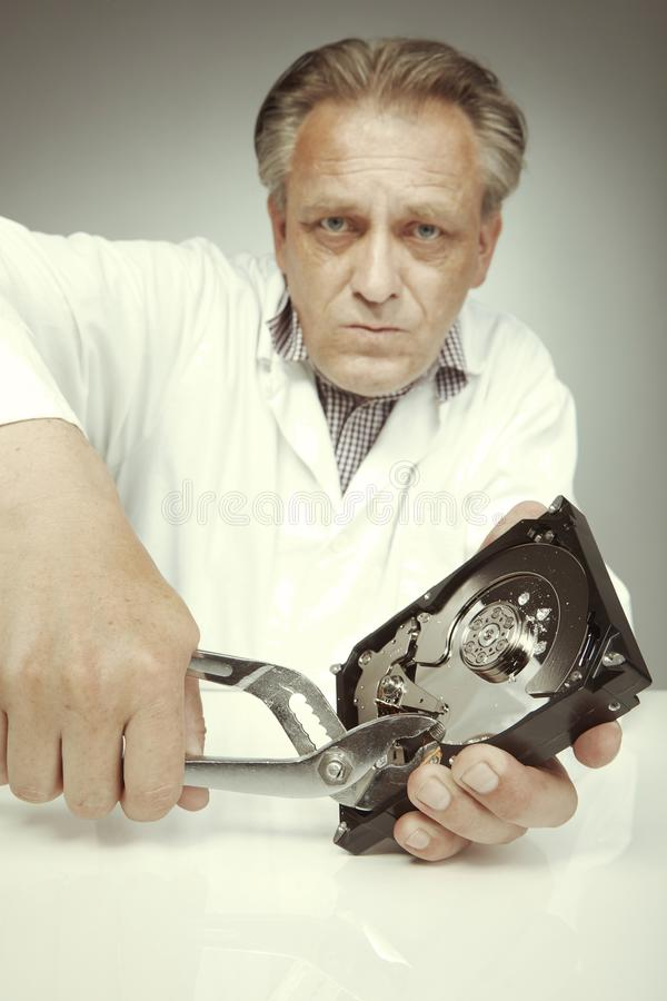 Especialista de la unidad de discos duros que borra datos de la unidad de discos duros con los alicates imagen de archivo