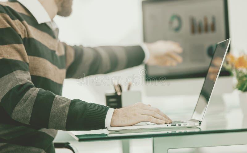 Especialista de las finanzas que trabaja en el ordenador port?til con las cartas financieras y foto de archivo libre de regalías