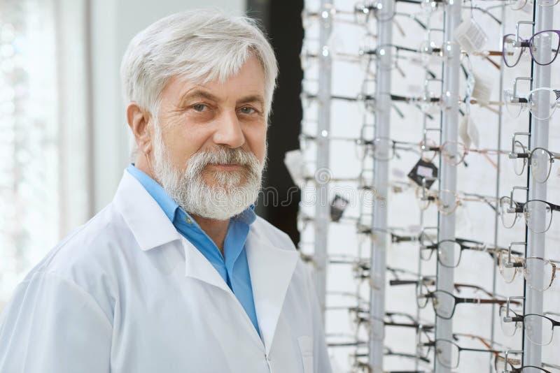 Especialista de olho de Expirienced que staing no gront do suporte com vidros fotos de stock royalty free