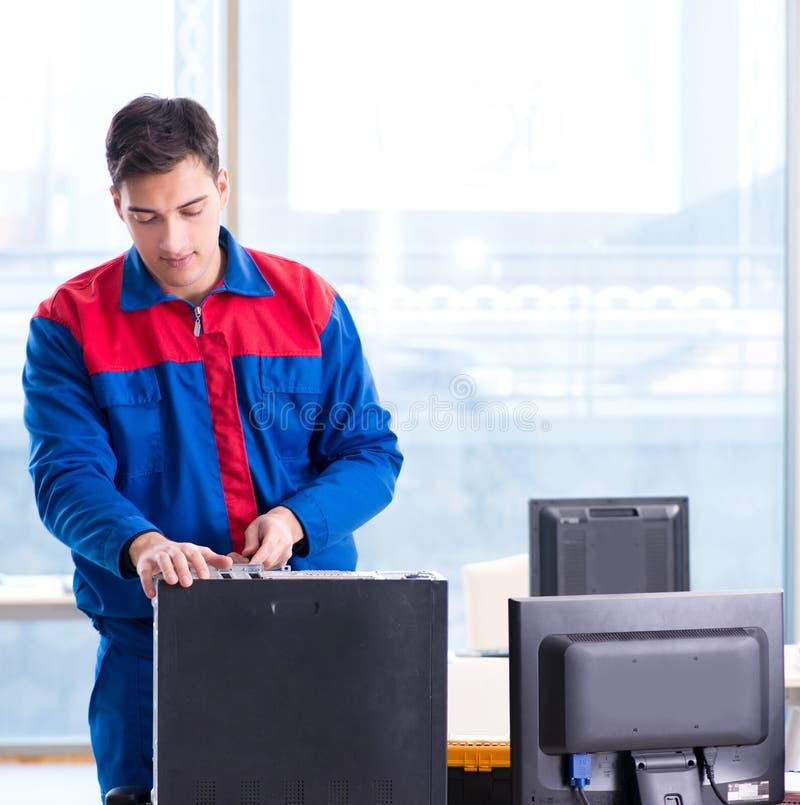 Especialista del reparador del ordenador que repara la mesa del ordenador fotografía de archivo