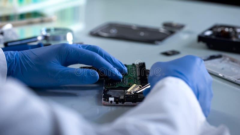 Especialista do hardware que analisa a peça do computador, experiência da ciência forense, ele fotografia de stock