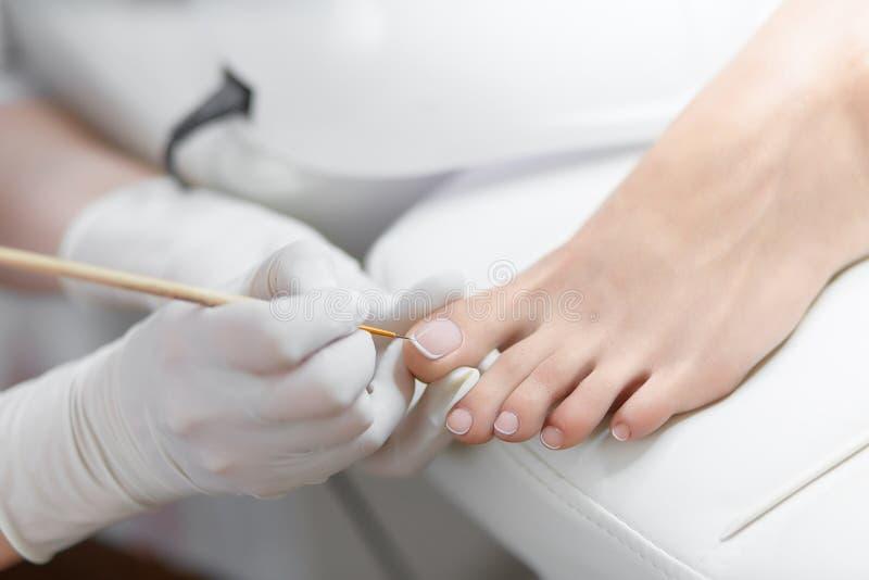 Especialista en el salón de belleza que hace la pedicura francesa para el cliente femenino fotos de archivo