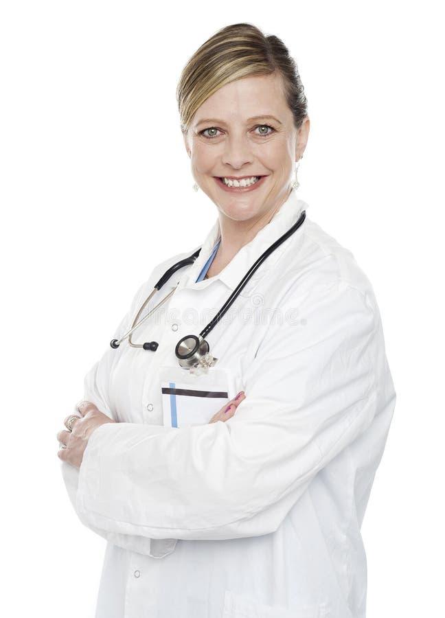 Especialista médico de sexo femenino que presenta con los brazos cruzados foto de archivo libre de regalías