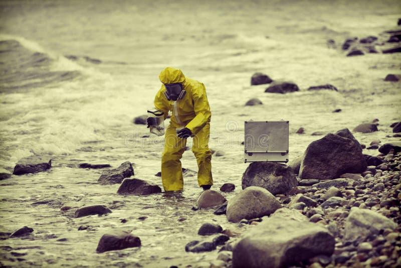 Especialista no terno protetor que toma a amostra de água ao recipiente imagens de stock
