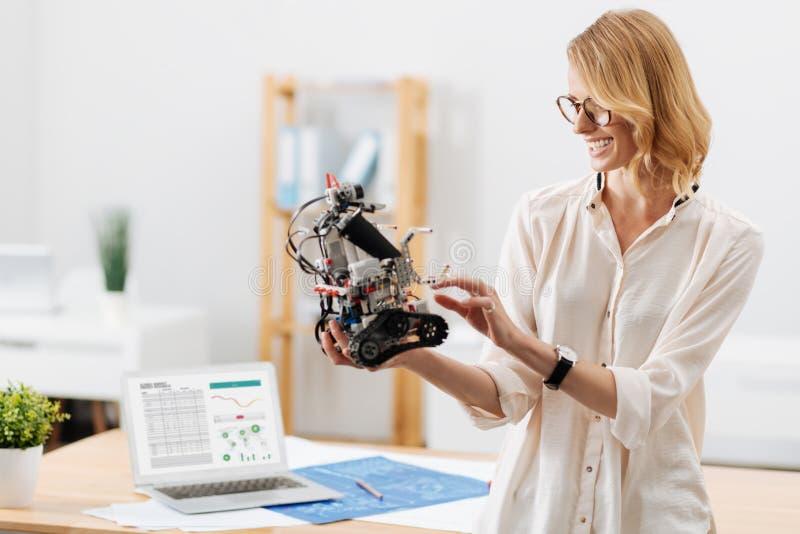Especialista positivo da tecnologia que testa pouco robô dentro foto de stock royalty free