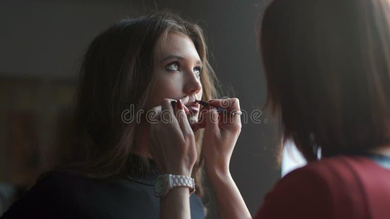 Especialista que hace el maquillaje para el modelo Apacible compense a la chica joven almacen de video