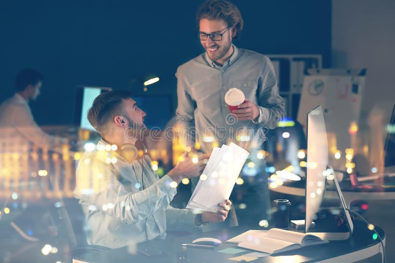 Especialistas de las TIC que intentan cumplir plazo en oficina tarde por la tarde fotografía de archivo libre de regalías