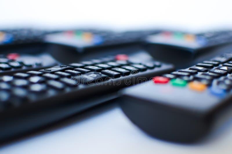Especialmente mandos a distancia negros pesadamente borrosos para la TV en un fondo blanco imagen de archivo libre de regalías