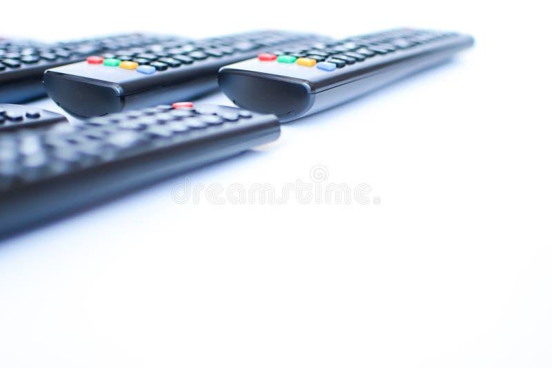 Especialmente mandos a distancia negros pesadamente borrosos para la TV en un fondo blanco imágenes de archivo libres de regalías