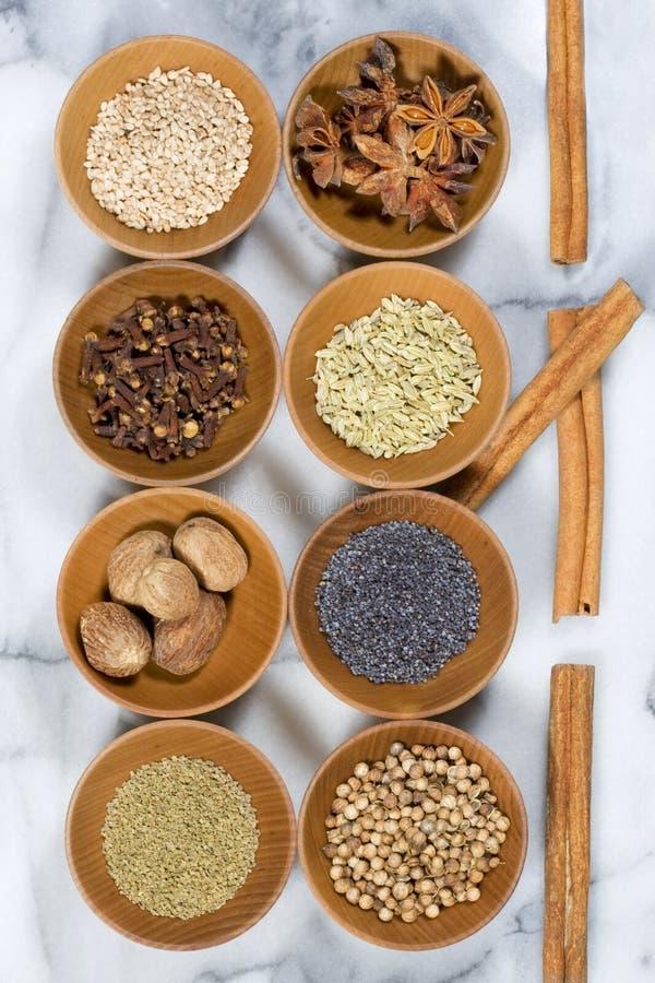 Especiarias & sementes nas bacias de madeira imagens de stock