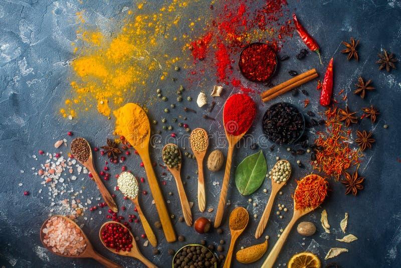 Especiarias coloridas em colheres, em sementes, em ervas e em porcas de madeira na tabela de pedra escura fotografia de stock royalty free