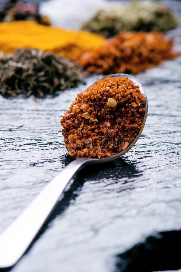 Especiarias e ervas diferentes em uma ardósia preta Colher do ferro com pimenta de pimentão Especiarias indianas Ingredientes par fotos de stock