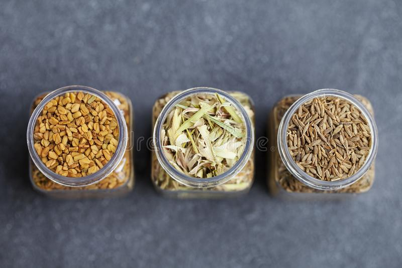 Especiarias em uns frascos, nardo, feno-grego, sementes de cominhos Fundo da ard?sia Vista superior imagem de stock royalty free