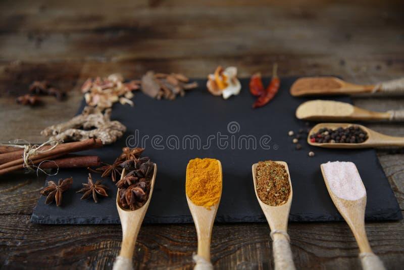 Especiarias tradicionais em colheres de madeira em uma placa de corte preta em um fundo rústico de madeira com espaço da cópia pa fotografia de stock royalty free