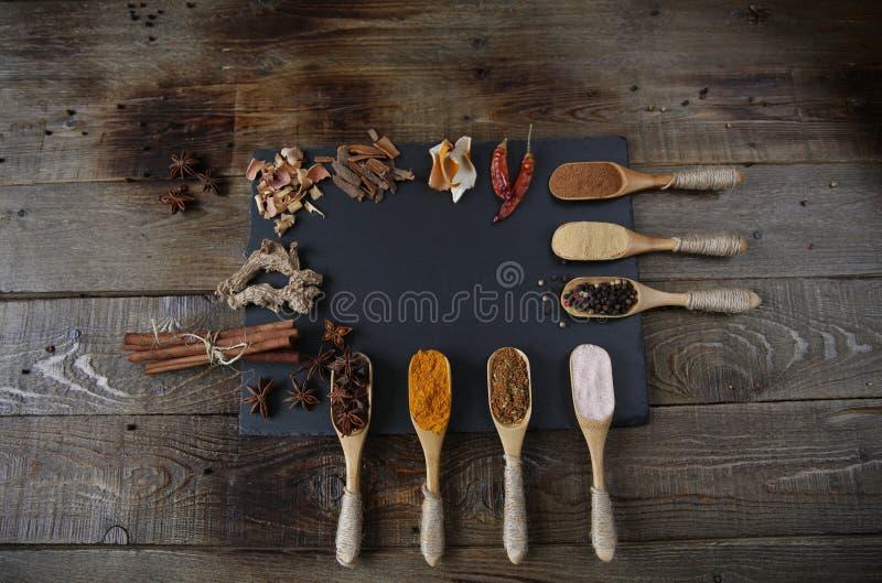 Especiarias tradicionais em colheres de madeira em uma placa de corte preta em um fundo rústico de madeira com espaço da cópia pa fotografia de stock