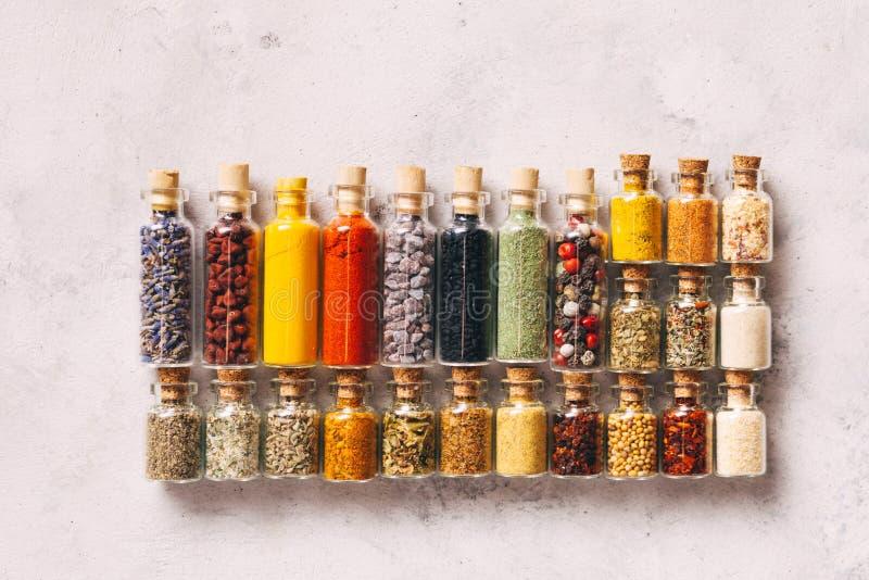 Especiarias trituradas em garrafas em fundo cinzento foto de stock royalty free