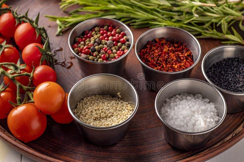 Especiarias: uma mistura das pimentas, dos flocos da paprika, do sal do mar, de tomates preto e branco do sésamo, dos alecrins e  foto de stock royalty free