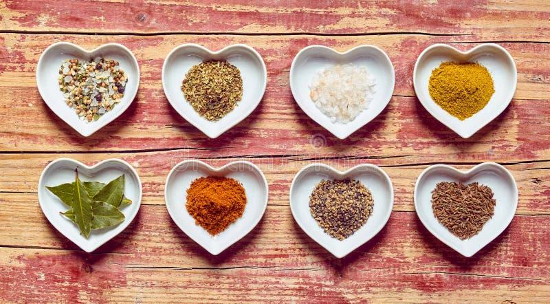 Especias culinarias clasificadas en platos en forma de corazón fotografía de archivo libre de regalías