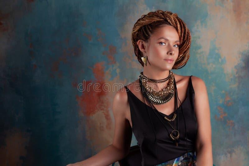 Especias del sur. Una bella joven de ojos azules con afrocos y grandes adornos contra la pared de estilo rústico texturizado fotos de archivo libres de regalías