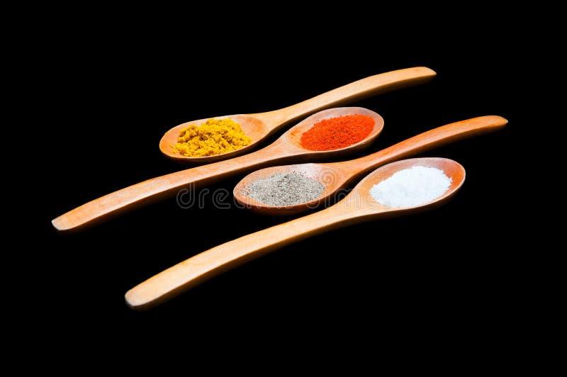 Especias en cucharas de madera imagenes de archivo