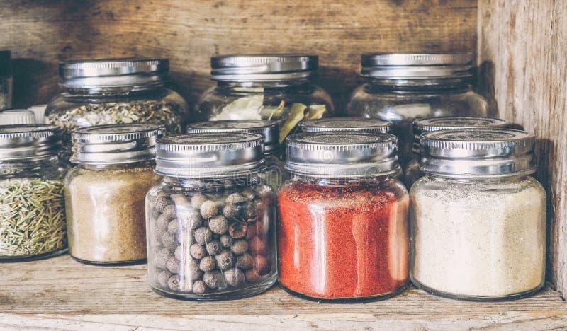 Especias en los tarros de cristal en el estante foto de archivo libre de regalías
