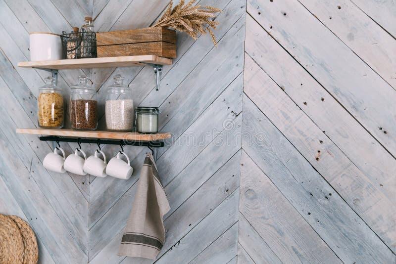 Especias en los tarros de cristal en estante, tazas blancas, caída de la toalla en los ganchos en la pared de la cocina imagen de archivo