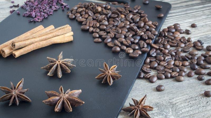 Especias y comida en fondo de madera Palillos de canela, anís de estrella y granos de café Ingredientes para la cocina casera foto de archivo libre de regalías